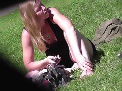 Присев на травке, барышня в платье светит киской перед вуайеристом